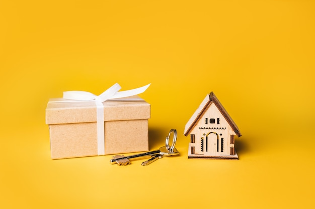 House miniature model, gift and keys on a yellow background. investment, real estate, home, housing