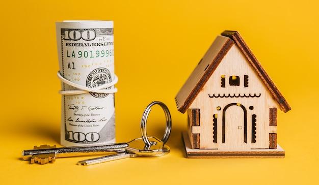 Миниатюрная модель дома, ключи и деньги на желтом фоне. инвестиции, недвижимость, дом, жилье