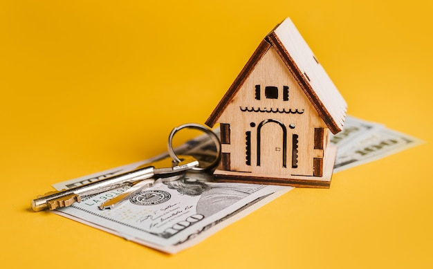 House miniature model, keys and money on a yellow background. investment, real estate, home, housing
