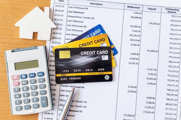 집 모델 및 은행 명세서 및 나무 테이블에 신용 카드에 계산기. 주택 구입 모기지 개념