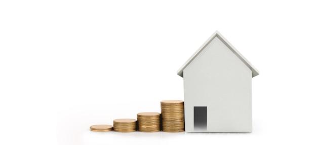 집 모형과 동전. 주택 및 부동산 개념. 홈 비즈니스 아이디어