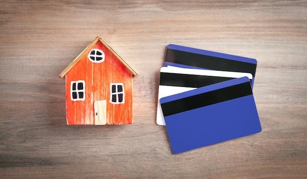 Модель дома и кредитная карта на деревянном столе.