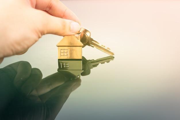 주택 보험 중개인 대리인 손 또는 판매원 사람에있는 집 모형 그리고 열쇠.