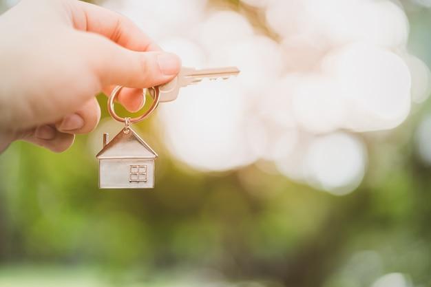 家のモデルと住宅保険ブローカーのエージェントの手のキー