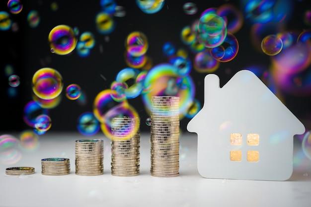 많은 거품과 흰색 테이블에 집 모델과 동전 돈의 행
