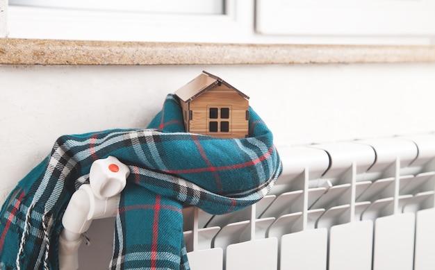 Модель дома и шарф на радиаторе дома зимой энергоэффективное отопление