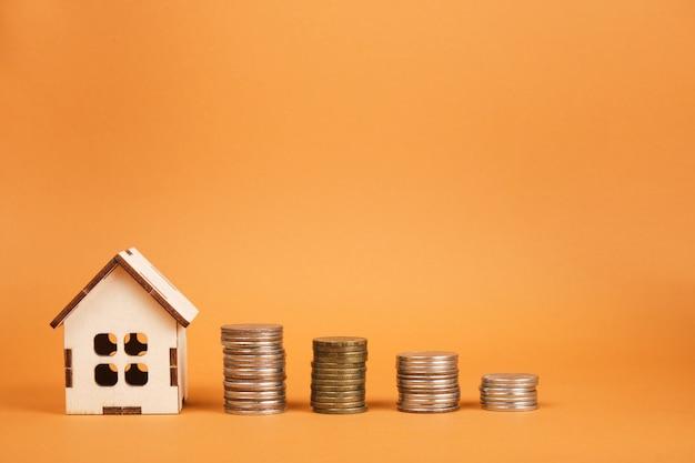 茶色の背景の不動産の概念上の家のモデルとコインの塔