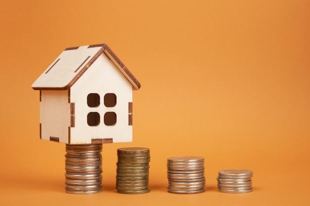 茶色の背景に家のモデルとコインの塔