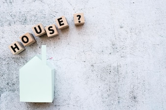 House model blocks with question mark sign over the paper model against grunge white wall
