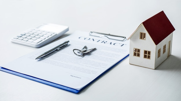 House model, calculator and house key lying on real estate contract