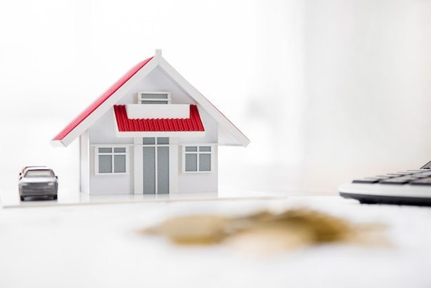House model and calculator on the table with blur pile of coins in foreground