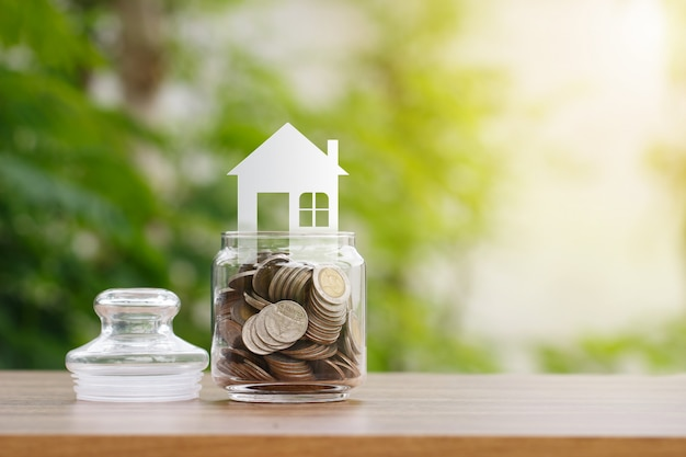 House model on coins in glass jar, saving to buy a house