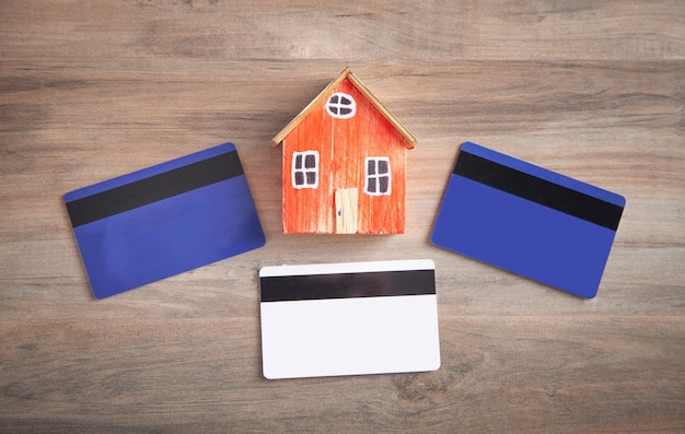 House model and credit card on the wooden table.