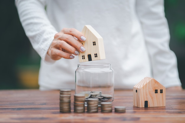 House model in hand with putting coins in jar step growing growth saving money, money stack in foreground