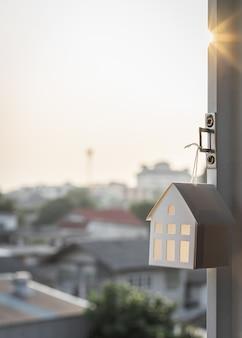 Модель дома висит на окне дома.