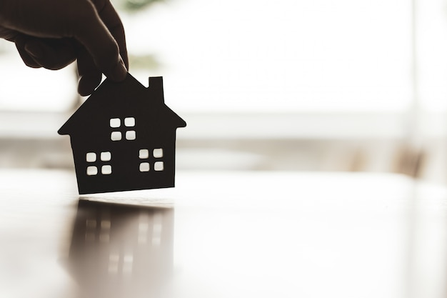 House model in home insurance broker agents hand or in salesman person.