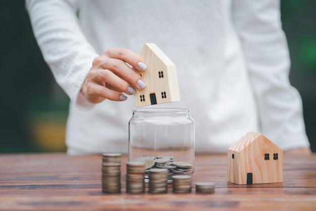 Модель дома в руке с помещением монет в банку, шаг роста, экономия денег, стопка денег на переднем плане