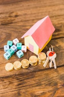 House model, key, math blocks and stacked coins on wooden backdrop