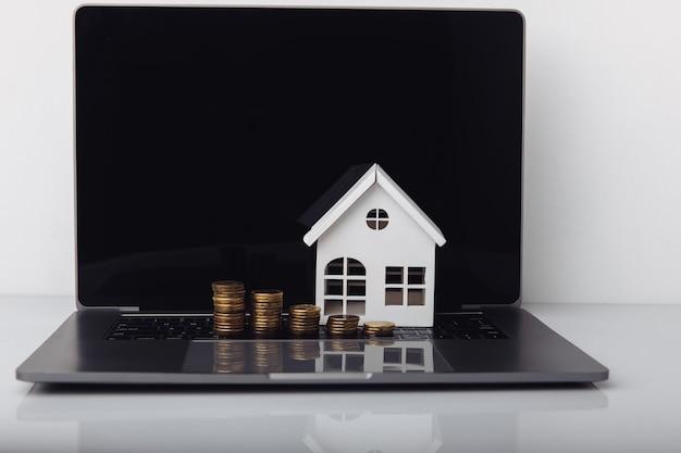 家のモデル、ラップトップ、コイン。住宅ローンの概念。
