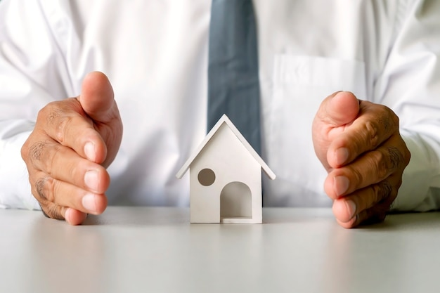 House model in male business hands, real estate concept, finance, borrowing, and mortgage.