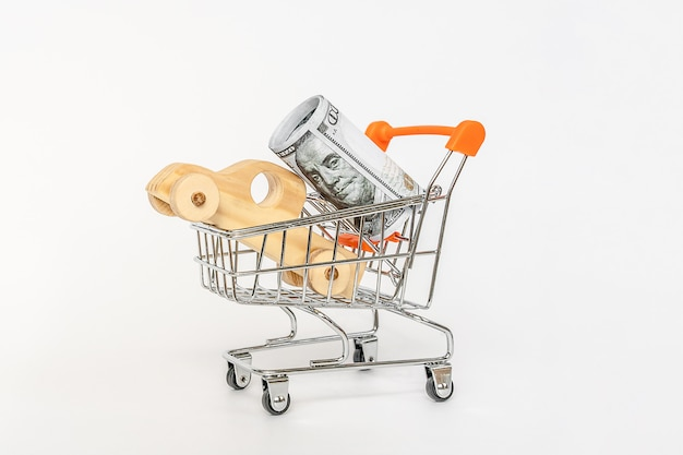 House model in mini shopping cart with stack of coins money on wooden table for residential investmen