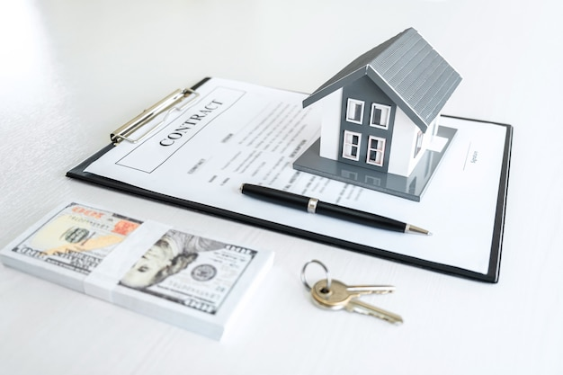 House model and money, house key lying on real estate contract