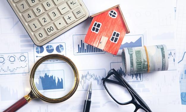 금융 그래프에 집 모델, 돈, 돋보기, 안경, 펜, 계산기.