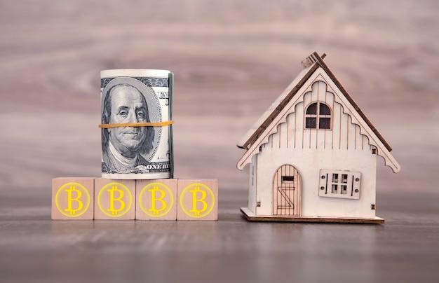 Модель дома, деньги, с символами биткойн на деревянном кубе.