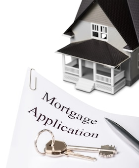 House model and mortgage application document with keys on white table