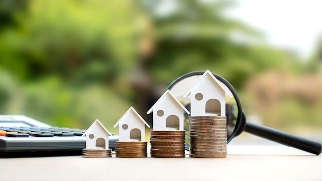 동전 더미에 있는 집 모델과 흐릿한 자연 녹색 배경. 부동산 투자 아이디어 모기지 및 주택 건설 이자율