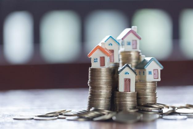 동전 스택에 집 모델입니다. 부동산 사다리, 모기지 및 부동산 투자에 대한 개념.