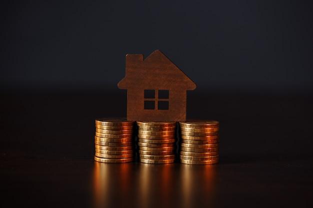 Модель дома на стеке монет. концепция инвестиций в недвижимость.