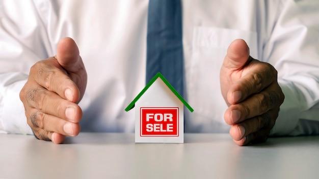 机の上に置かれた家のモデルと金融コンセプトの家のモデルを包むビジネスマンの手。住宅ローンと不動産