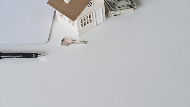 House model, rental agreement or house purchase agreement, money, paper, pen and the property's key on the white desk.