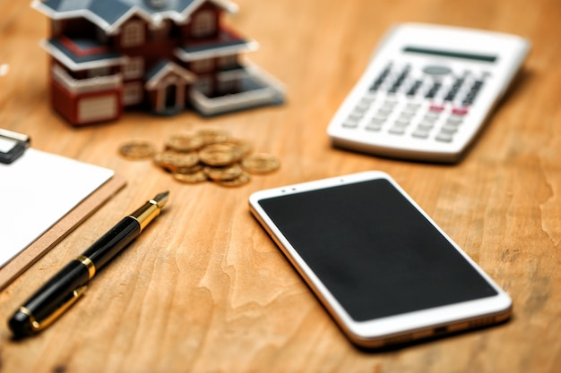 House model ,smartphone ,calculator and golden coins on wooden table