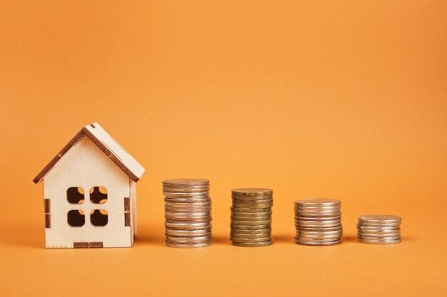 House model and towers of coins on a brown background