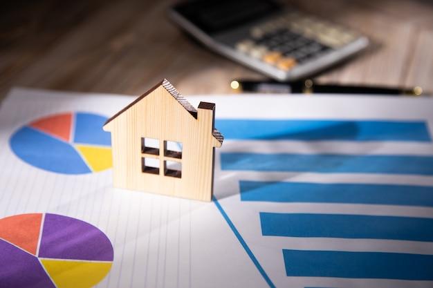 Модель дома с калькулятором и графиком на столе