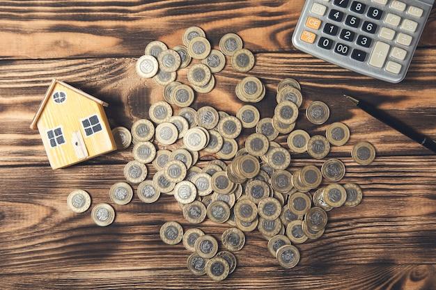 동전과 계산기 테이블에 집 모델입니다. 부동산 중개인 서비스