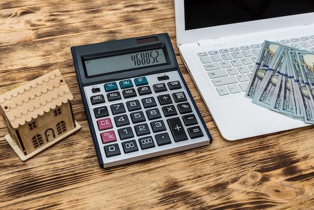 ドル、ラップトップ、クリップボードを備えた家のモデル