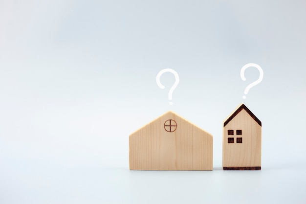 House model with question marks on blue background loan concept