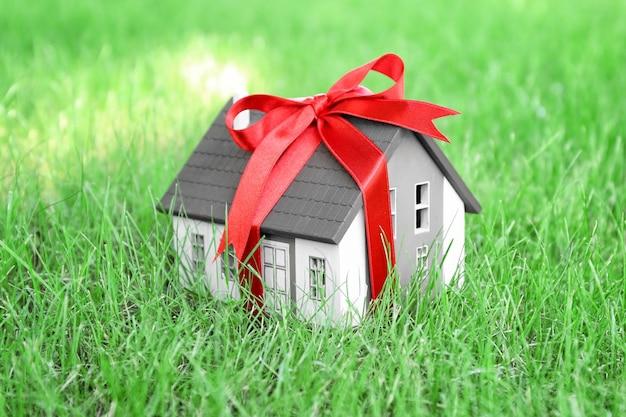 Модель дома с лентой на зеленой лужайке. концепция ипотеки