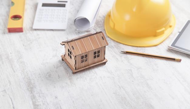 Модель дома с инструментами на белом фоне