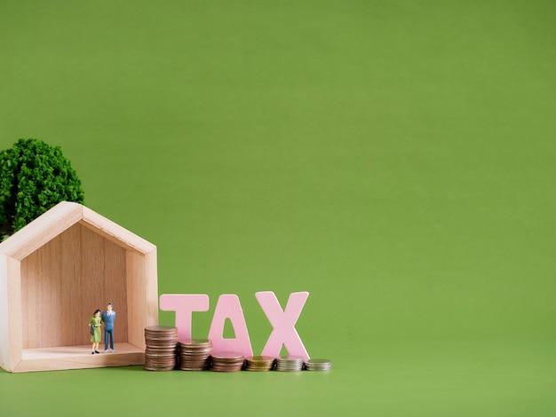 単語tax、ミニチュアの人々と緑の背景にコインを持つ家のモデル。テキスト用のスペース