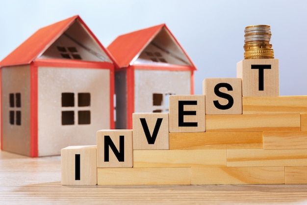 House models and inscription on wooden cubes - invest. real estate investment concept.