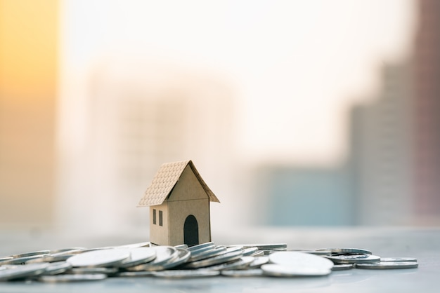 House models on pile of coin with city backgrounds.