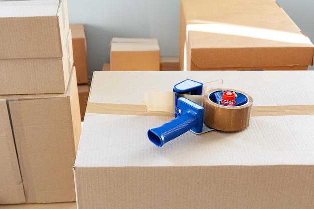 Концепция переезда дома со сложенными картонными коробками в комнате