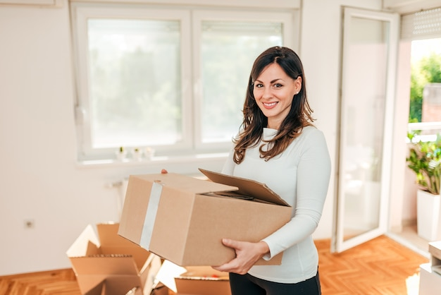 House moving concept. woman holding cardboard box, looking at camera.