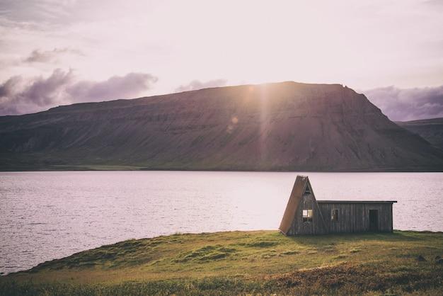 白い空の下の湖の近くの家