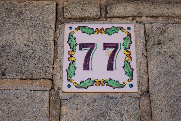 House number seventy-seven 77 painted on ceramic tile in blue and black with fleur-de-lis pattern from sweden or belgium.