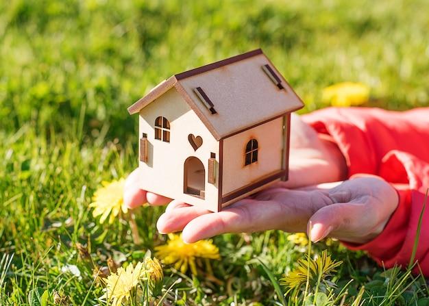 Дом на ладонях на зеленой траве и жёлтых одуванчиках